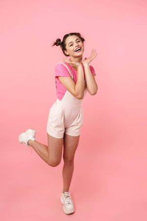 Full length of a pretty young teenage girl jumping isolated over pink background, rejoycing