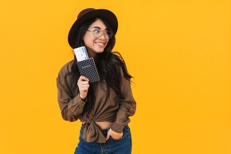 Cheerful young asian woman showing passport with flight tickets isolated over yellow background