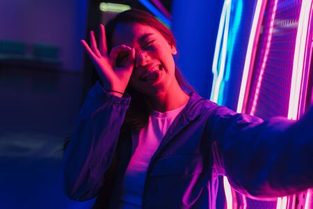 Beautiful young asian woman with long dark hair standing infront of a neon wall Banque d'images