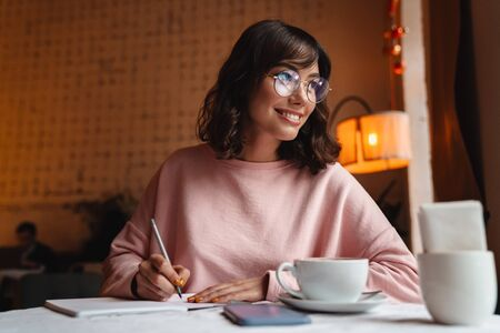 Photo of a beautiful pretty happy brunette young woman indoors in cafe writing notes in notebook.