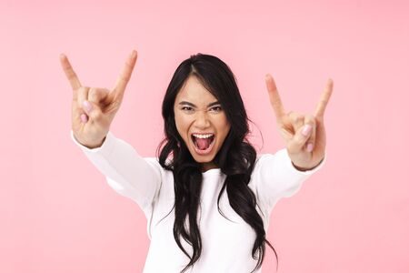 Cheerful young asian woman showing horns up gesture isolated over pink background Banque d'images