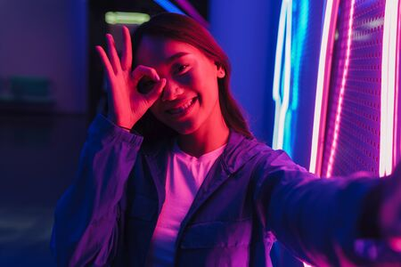 Beautiful smiling young asian woman with long dark hair standing infront of a neon wall, taking a selfie, showing ok gesture Banque d'images