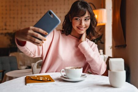 Photo of a happy smiling brunette young woman indoors in cafe drinking coffee using mobile phone take a selfie.