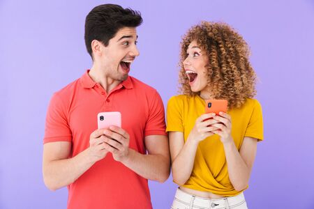 Portrait of excited caucasian people man and woman in basic clothing rejoicing while using cellphones together isolated over violet background