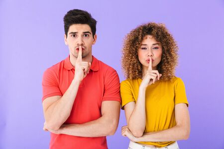 Portrait of serious caucasian people man and woman holding index fingers on lips and asking be quiet isolated over violet background