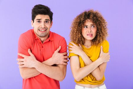 Portrait of displeased frozen caucasian people man and woman wearing t-shirts shaking and trembling from cold isolated over violet background