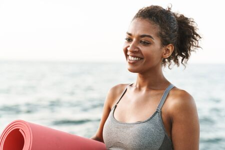 Photo of joyful african american sportswoman in tracksuit smiling and standing with yoga mat by seaside in morning Banco de Imagens