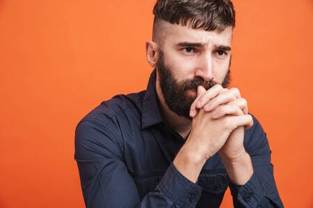Image closeup of uptight man with nose jewelry wearing black shirt thinking with fists clenched isolated over orange background Banco de Imagens