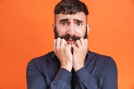 Image closeup of uptight man with nose jewelry wearing black shirt grabbing his face in fear isolated over orange background Banco de Imagens