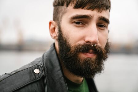 Photo closeup of bearded young man wearing leather jacket looking at camera outdoors