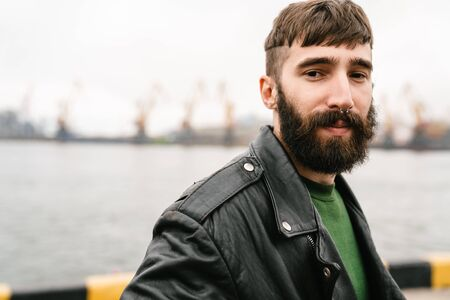Photo closeup of bearded young man wearing leather jacket looking at camera while standing in sea port Фото со стока
