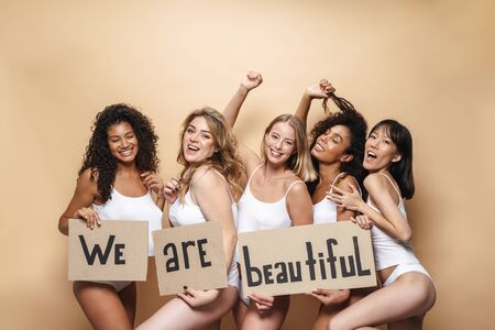 Image of young multinational women in underclothes making fun and holding placards isolated over beige