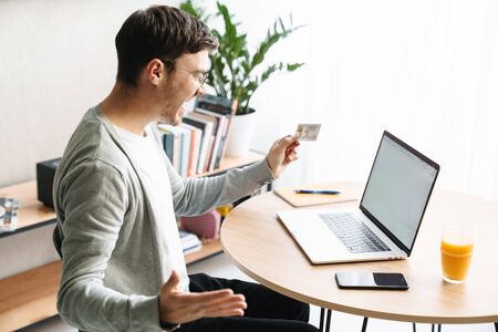 Image of happy young man smiling and holding credit card while making payment online with laptop at home Фото со стока