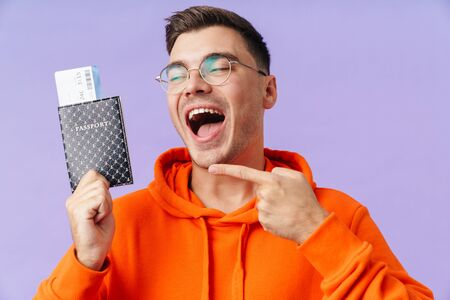 A positive happy young man holding passport with tickets pointing.