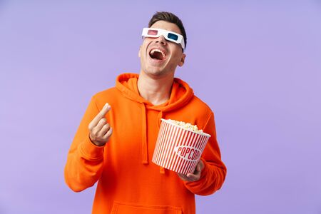 Photo of laughing happy young man posing isolated over purple background wearing 3d glasses eat popcorn.