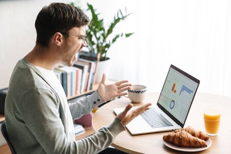 Image of angry young man in eyeglasses screaming and looking at screen while working on laptop at home Фото со стока