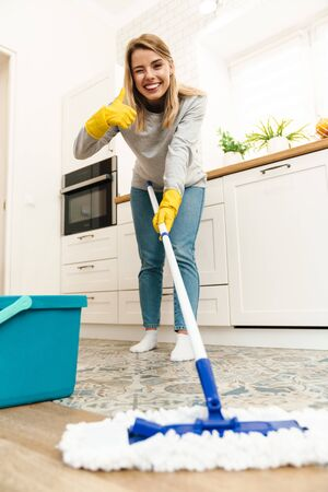 Photo of joyful young woman housewife in gloves gesturing thumb up and winking while mopping floor at kitchen