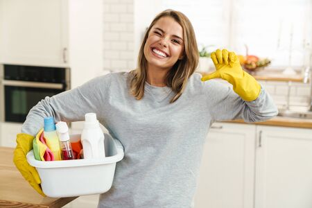 Photo of smiling young woman housewife in gloves holding cleanser bottles and showing thumb down at modern kitchen