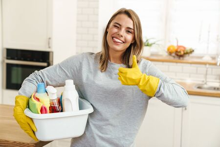Photo of smiling young woman housewife in gloves holding cleanser bottles and showing thumb up at modern kitchen Zdjęcie Seryjne