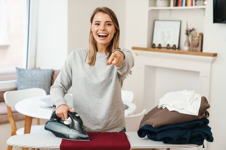 Photo of cheerful young beautiful woman housewife pointing finger at camera while ironing clothes at living room