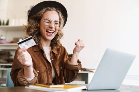 Image of delighted young woman in hat making winner gesture and holding credit card while working with laptop
