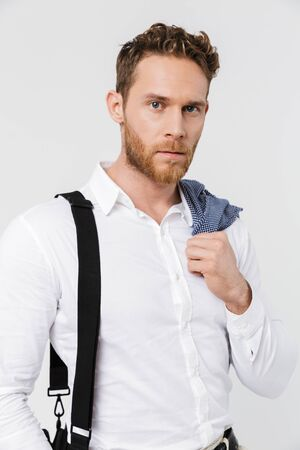 Image of bearded blonde man holding jacket and looking at camera isolated over white background Imagens