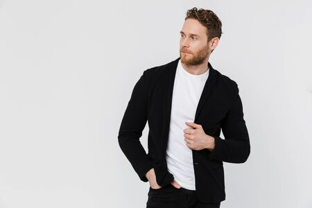 Image of unshaven serious man in jacket posing and looking aside isolated over white background Imagens