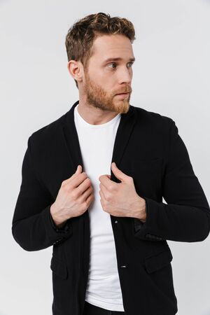Image of handsome serious man in jacket posing and looking aside isolated over white background