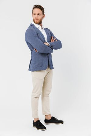 Image of serious young man wearing jacket posing and looking aside isolated over white background