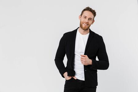 Image of handsome pleased man in jacket smiling and posing on camera isolated over white background