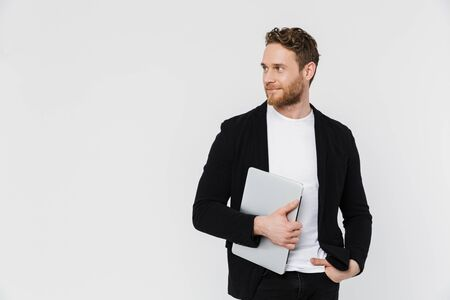 Image of handsome pleased man in jacket smiling and holding laptop isolated over white background