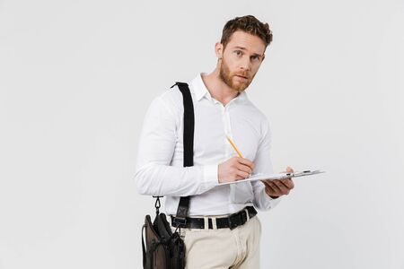 Image of focused young man holding clipboard and writing isolated over white background