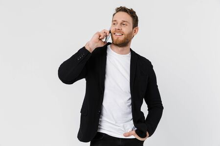 Image of handsome joyful man in jacket laughing and talking on smartphone isolated over white background