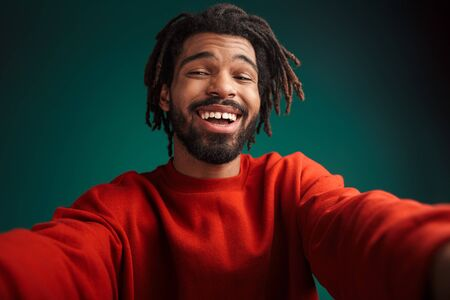 Portrait of joyful african american man laughing while taking selfie photo isolated over green background