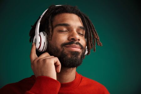 Portrait of pleased african american man smiling and using wireless headphones isolated over green background