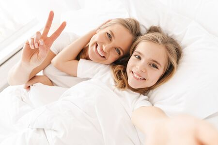 Photo of blonde cheerful mother with daughter gesturing peace sign and taking selfie while lying in white bad Banque d'images