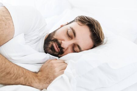 Image of young unshaven caucasian man sleeping alone in bed with white linen at home