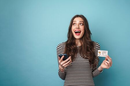 Photo of excited nice woman in striped sweater holding credit card and cellphone isolated over blue wall