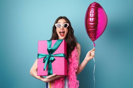 Photo of delighted young woman in sunglasses posing with balloon and gift box isolated over blue wall