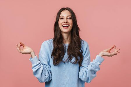 Image of attractive young woman with long brown hair meditating and keeping fingers together isolated over pink background