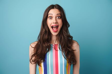 Photo of excited nice woman in striped dress expressing surprise at camera isolated over blue wall