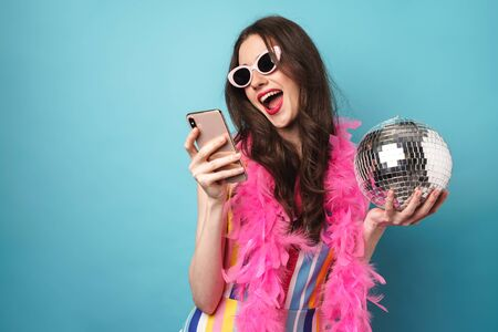 Photo of joyful young woman in sunglasses using smartphone and holding disco ball isolated over blue wall