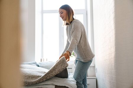 Smiling attractive blonde girl making bed in the morning