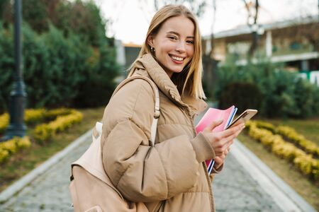 Portrait of smiling young woman holding exercise books and using mobile phone while walking in park Фото со стока