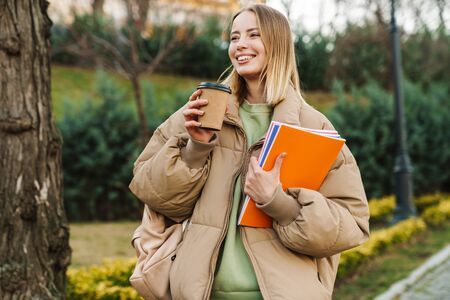 Portrait of smiling young woman holding exercise books and drinking coffee takeaway while walking in park