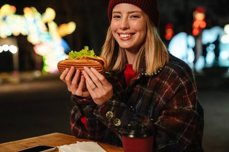 Photo of happy nice woman smiling and eating sandwich while sitting in street cafe outdoors