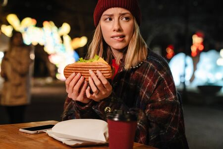 Photo of scared nice woman eating sandwich while sitting in street cafe outdoors Stock fotó
