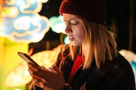 Photo of displeased nice woman typing on mobile phone while walking at park with neon lighting