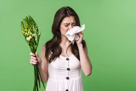 Image of unhappy young woman with allergy holding handkerchief and flowers isolated over green background