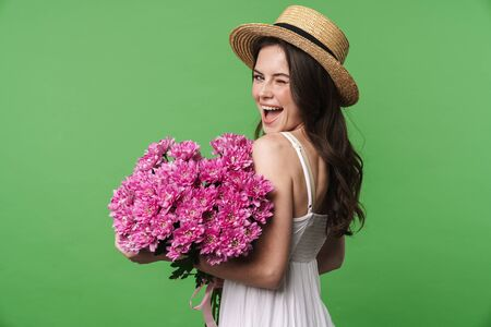 Image of excited pretty woman in straw hat winking and holding flowers isolated over green background